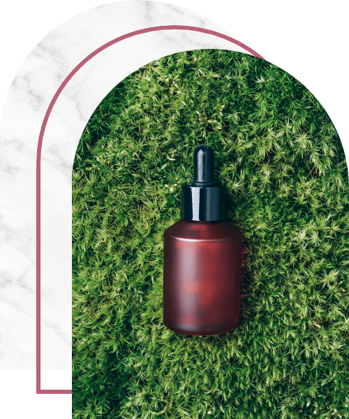 Red glass cosmetic bottle on grass
