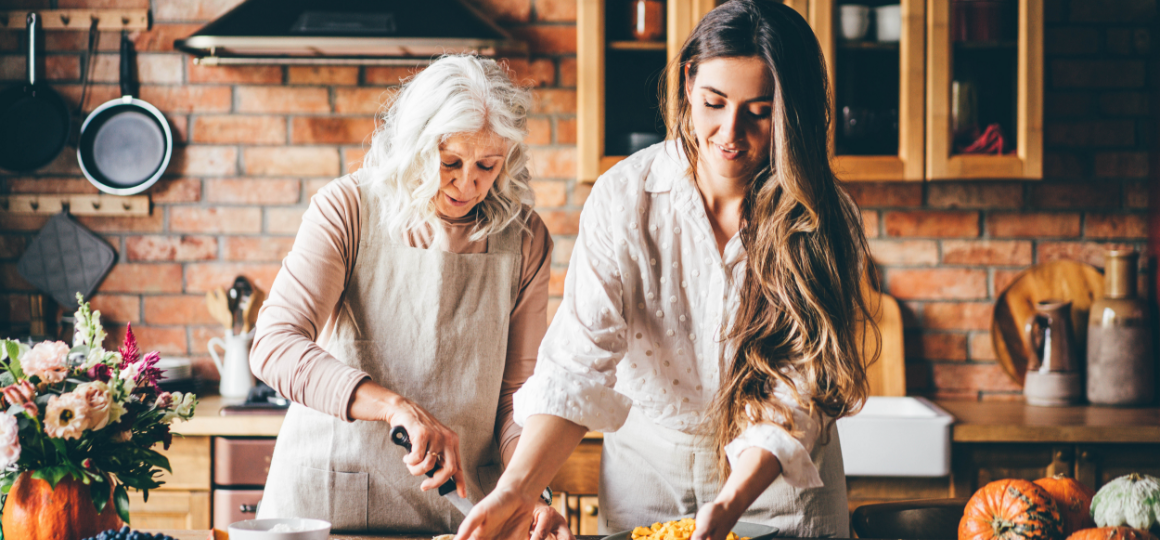 Senior mother and happy adult daughter baking pumpkin pie together at home