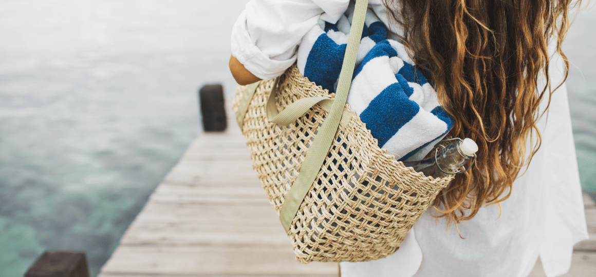 Woman with handmade wicker bag at pier