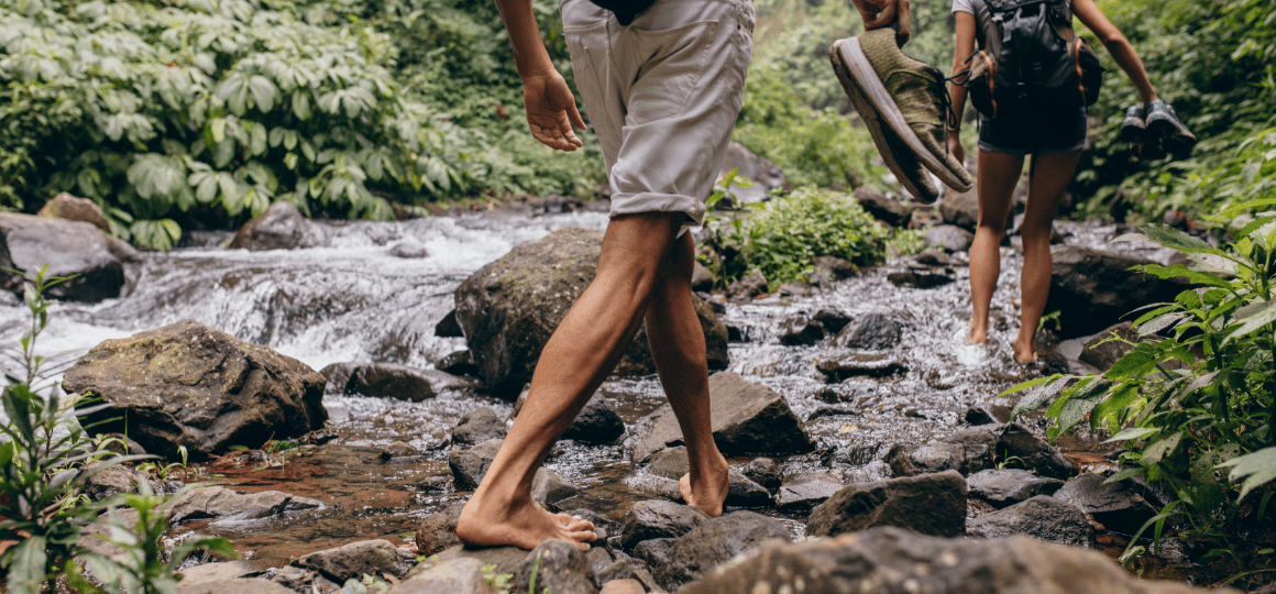 Man and woman crossing the stream barefooted