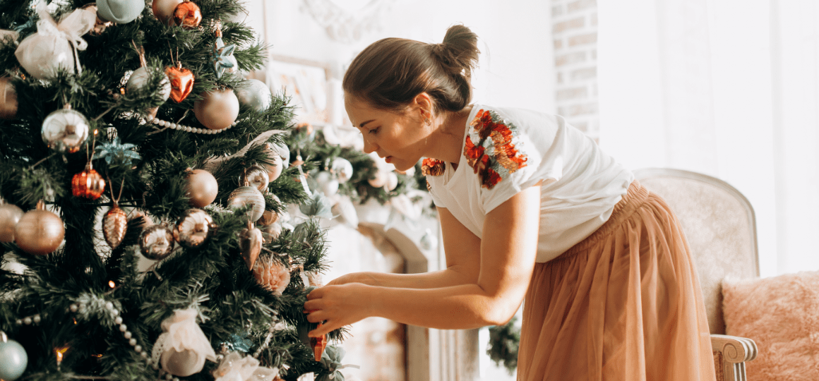 Young beautiful woman decorates a New Year's tree in the full of light cozy room