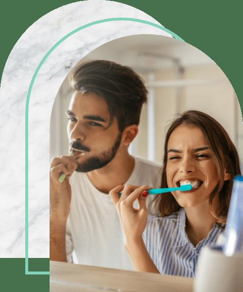 Happy couple bonding while brushing teeth in the bathroom