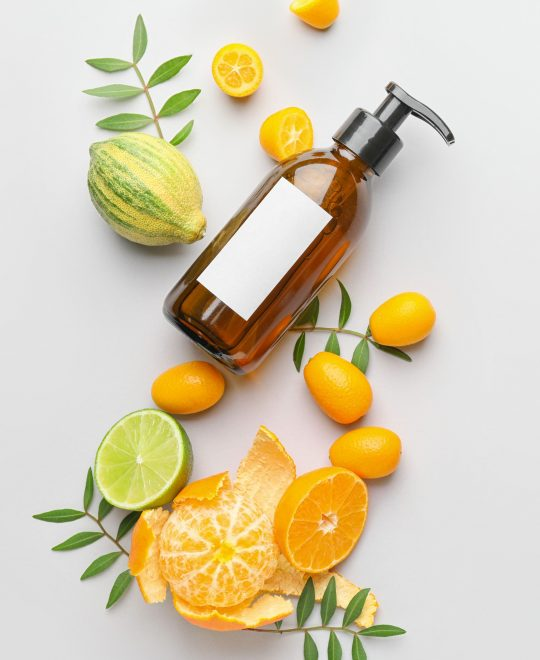 Cosmetic product in bottle and citrus fruits on white background