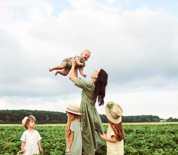 Mother with children in a linen dress with a basket of strawberries gathers a new crop and has fun with the children
